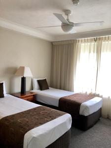 A bed or beds in a room at Bougainvillea Gold Coast Holiday Apartments