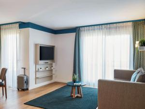 A television and/or entertainment center at Aparthotel Adagio Monaco Palais Joséphine