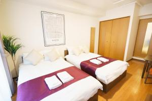 A bed or beds in a room at Rejoice Stay Karasumaoike