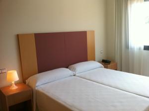 A bed or beds in a room at Hotel-Apartamentos Tartesos