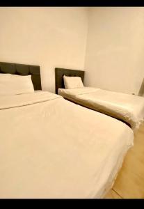 A bed or beds in a room at Durrat Al-Arus Dahaban Apartments
