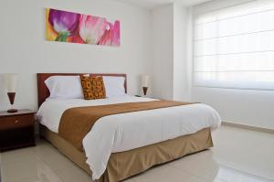 A bed or beds in a room at 122 Plaza Apartahotel