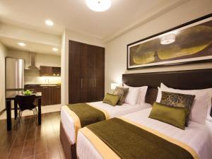 Кровать или кровати в номере Mövenpick Hotel Apartments Al Mamzar Dubai