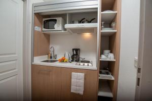 A kitchen or kitchenette at Privilodges Le Royal - Apparthotel