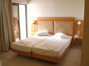 A bed or beds in a room at Saint Constantine Hotel
