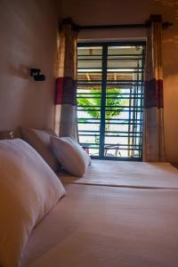 A bed or beds in a room at Yoho Hikkaduwa Beach House