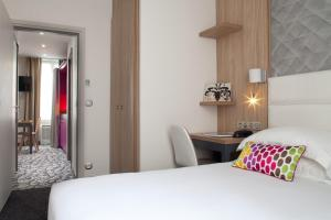A bed or beds in a room at Serotel Suites Opera