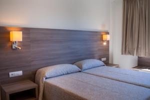 A bed or beds in a room at Apartamentos Tres Torres