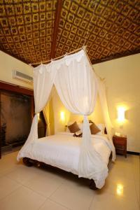 A bed or beds in a room at Putu Bali Villa & Spa