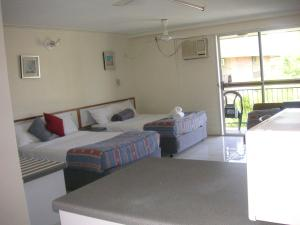 A bed or beds in a room at Cairns Holiday Lodge