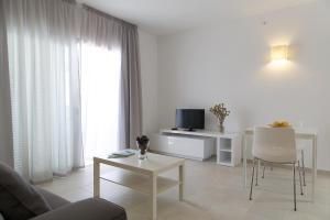 A television and/or entertainment center at Apartaments Proa Es Pujols ( Only Adults )