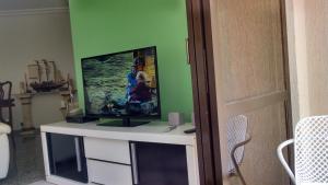 A television and/or entertainment center at Apartamento Enseada Guarujá