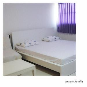 A bed or beds in a room at IMPACT Don Mueang Bangkok Guest House