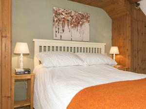 A bed or beds in a room at Bwthyn Bach Holiday Cottage