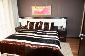 A bed or beds in a room at Горки Город Апартаменты