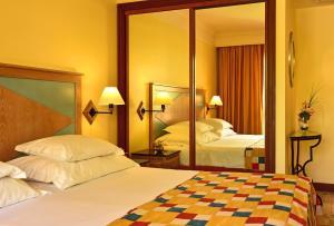 Een bed of bedden in een kamer bij Pestana Miramar Garden & Ocean Hotel