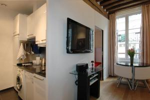 A television and/or entertainment center at HolidaysInParis-Bourg Tibourg II