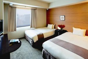 A bed or beds in a room at Citadines Central Shinjuku Tokyo