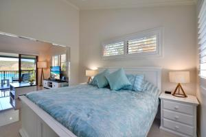 A bed or beds in a room at Heliconia Grove on Hamilton Island