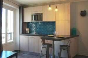 A kitchen or kitchenette at thesuites Paris Studios