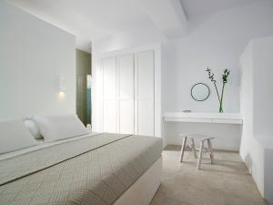 A bed or beds in a room at Unique Milos Suites