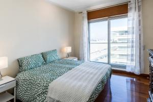 A bed or beds in a room at Sea View Apartment Carlos Carvalho