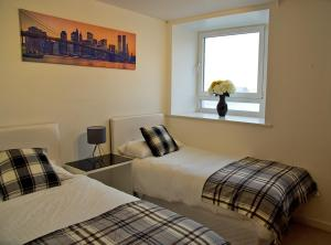 A bed or beds in a room at Central Brentwood - Essex Apartments