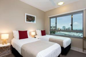 A bed or beds in a room at Darwin Executive Suites & FREE CAR