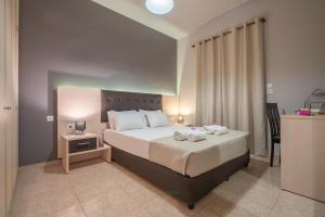 A bed or beds in a room at Armonia Boutique Hotel