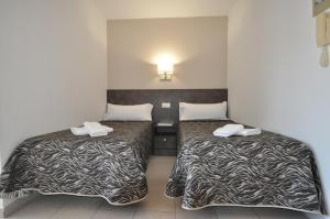 A bed or beds in a room at Aparthotel Safari