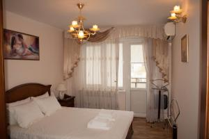 A bed or beds in a room at YaltaLux Apartments