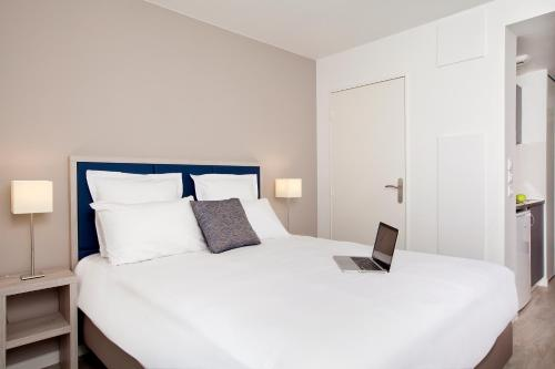A bed or beds in a room at Sejours & Affaires Paris-Davout