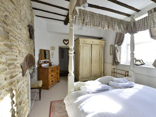 A bed or beds in a room at Kemble Cottage