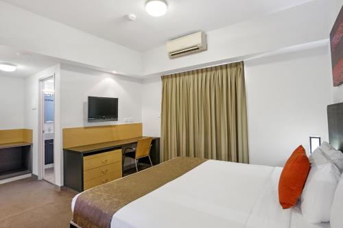 A bed or beds in a room at Toowong Inn & Suites