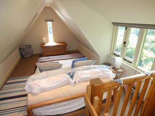 A bed or beds in a room at The Garden Cottage, Weymouth
