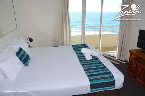 A bed or beds in a room at Zenith Ocean Front Apartments