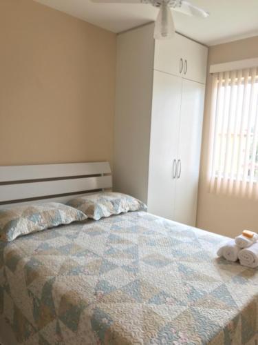 A bed or beds in a room at Apto a 200m da Praia, condomínio clube