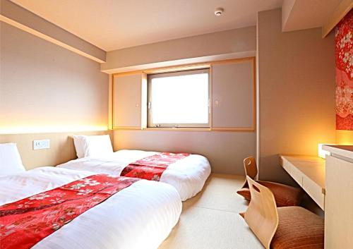 A bed or beds in a room at Hotel Wing International Premium Kanazawa Ekimae