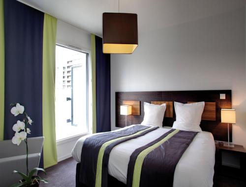 A bed or beds in a room at Lagrange Apart'Hotel Paris-Boulogne
