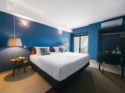 Een bed of bedden in een kamer bij Topazio Mar Beach Hotel & Apartments