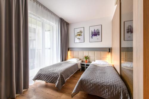 A bed or beds in a room at City Comfort Aparthotel