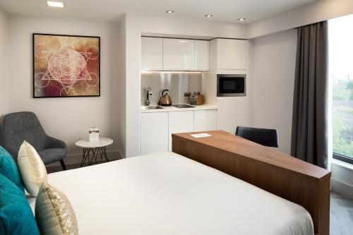 A bed or beds in a room at Roomzzz London Stratford