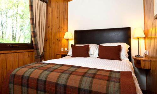 A bed or beds in a room at Macdonald Lochanhully Resort