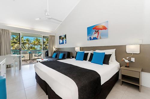 A bed or beds in a room at By The Sea Port Douglas