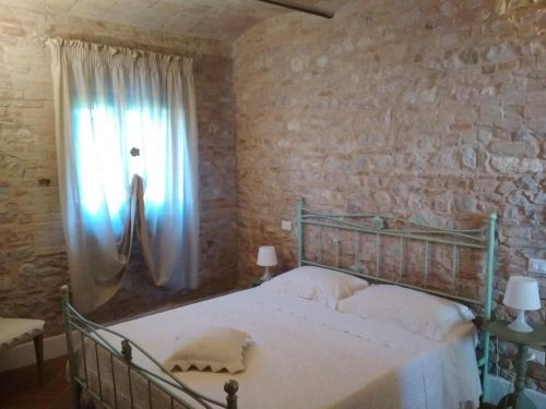 Podere Le Volte degli Angeli tesisinde bir odada yatak veya yataklar