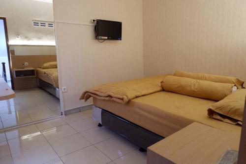 A bed or beds in a room at deRollas Villa Batu