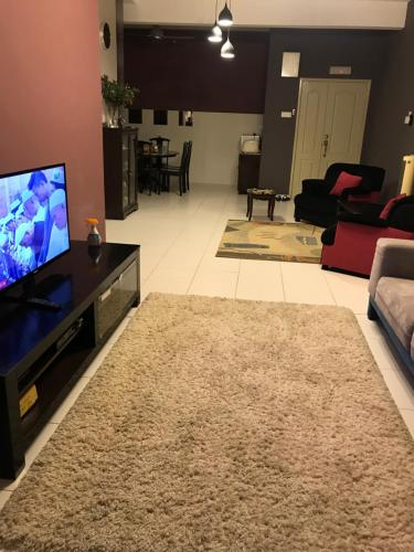A television and/or entertainment centre at 1-World Condo - Tok Bali Place