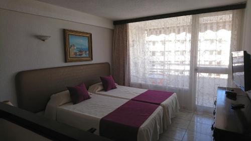 Een bed of bedden in een kamer bij Apartamentos Borinquen