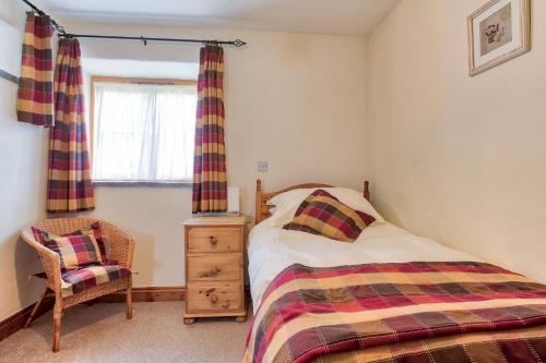 A bed or beds in a room at Tregolls Farm Cottages