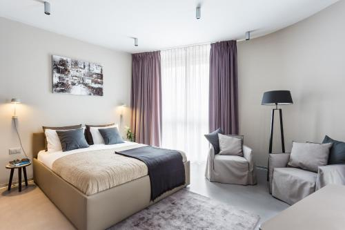 A bed or beds in a room at VISIONAPARTMENTS St. Sulpice Route de Vallaire